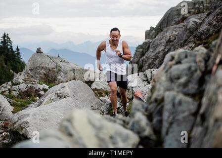 Excursionista macho que se ejecuta a través de las rocas, la Montaña del Perro, BC, Canadá Imagen De Stock