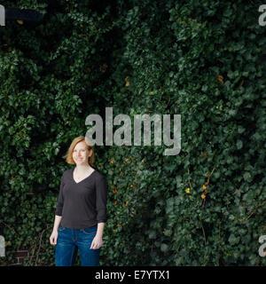 Mujer de pie contra el follaje de hiedra Imagen De Stock