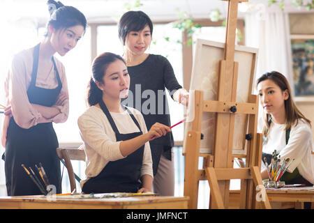 Profesor de Arte con mujeres jóvenes en studio Imagen De Stock