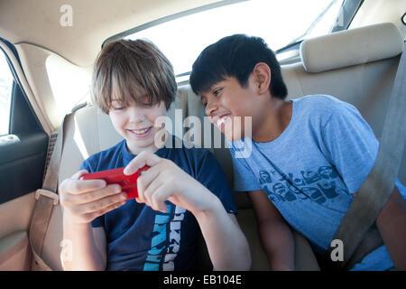 Dos muchachos de 10 años ver un vídeo en un teléfono, el asiento trasero de un coche. Imagen De Stock