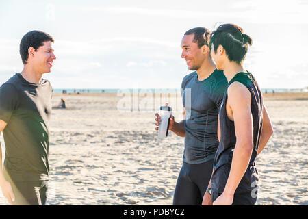 Deslizadera macho amigos descansando, hablando en sunny beach Imagen De Stock