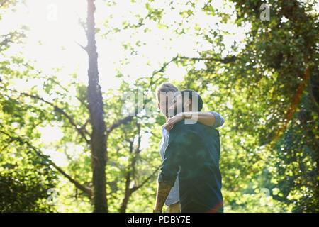 Una pareja gay afectuoso abrazo y caminar en el parque soleado Imagen De Stock