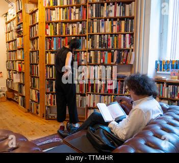 Hombre leyendo libro inside St Georges librería de segunda mano en Prenzlauer Berg, Berlín, Alemania Imagen De Stock