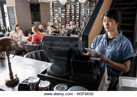 Camarera con tableta digital trabajando en caja registradora en restaurante. Imagen De Stock