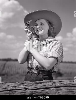 1940 sonriente joven mujer con sombrero de cowboy y fotografiar usando ropa OCCIDENTAL DE MANO CÁMARA DE CINE EN CASA 8MM - u532 HAR001 HARS HOBBY OCIO INTERÉS Y EMOCIÓN AFICIONES CONOCIMIENTO pasatiempo recreativo fotografiar placer en sonrisas con gozosa conceptual elegante 8MM RELAJACIÓN Mano mujer adulta joven amateur EN BLANCO Y NEGRO la etnia CAUCÁSICA GOCE HAR001 ANTICUADO Imagen De Stock