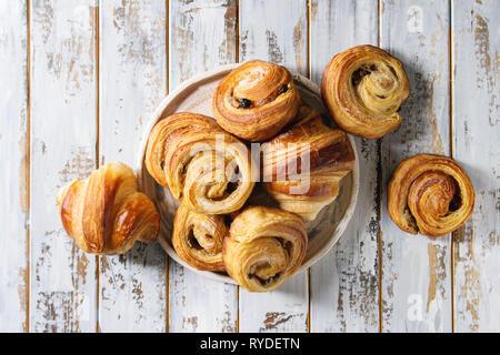 Variedad de bollos de hojaldre casera rollos de canela y croissant en placa de cerámica blanca sobre fondo de madera del tablón. Espacio laical, plana Imagen De Stock