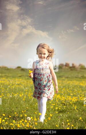 Una niña de 3 años de edad ejecutando a través de una pradera de flores Imagen De Stock
