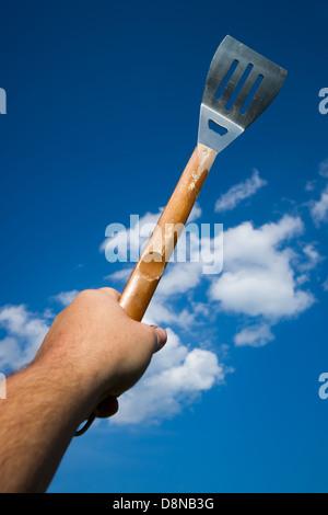 Un hombre mano sostiene una espátula para barbacoa aloft contra un cielo azul con nubes esponjosas. Imagen De Stock