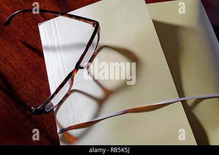 Carpeta de archivo de amarillo y gafas de lectura sobre el escritorio de oficina Imagen De Stock