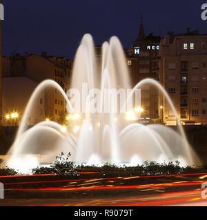 España, Asturias, Oviedo, vista nocturna de una fuente artificial en una rotonda de la ciudad Imagen De Stock
