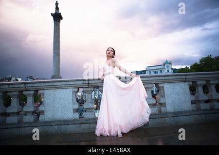 Retrato de mujer joven en vestido de noche al anochecer, Trafalgar Square, Londres, Reino Unido. Imagen De Stock