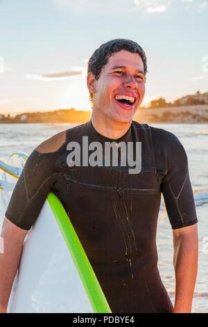 Laughing macho surfer con tablas de surf en la playa Imagen De Stock