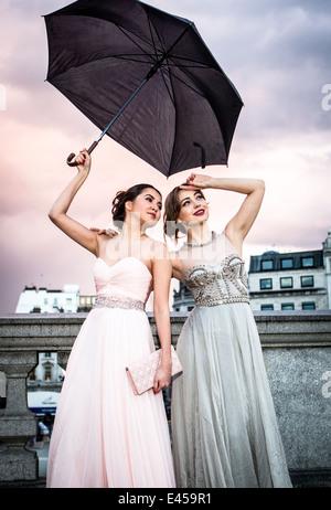 Retrato de dos mujeres modelos posando con sombrilla, Trafalgar Square, Londres, Reino Unido. Imagen De Stock