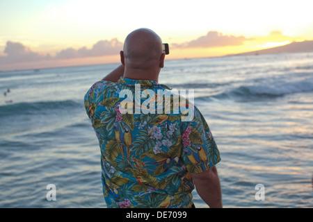Turista en Hawaii toma una foto de la puesta de sol del océano con su teléfono. Imagen De Stock