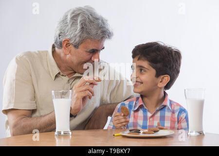 Abuelo y nieto de comer galletas con un vaso de leche Imagen De Stock