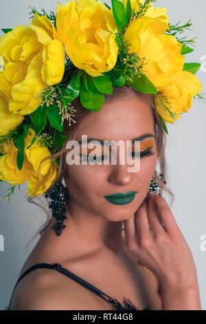Retrato de moda de una hermosa chica rubia con una corona de flores amarillas grandes sobre su cabeza y maquillaje brillante sobre un fondo gris Imagen De Stock