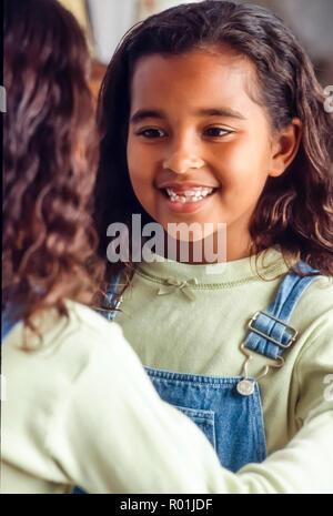 Niña mira a diente que falta en el espejo. © Myrleen Pearson .......Ferguson Cate Imagen De Stock