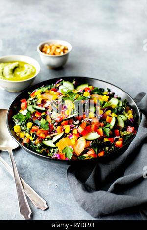 Kale ensalada de verduras con vinagreta de pesto de perejil. Fotografiado sobre un fondo gris. Imagen De Stock