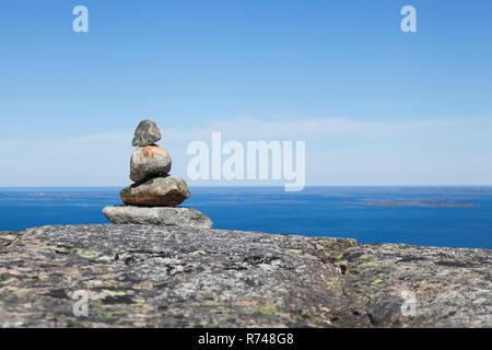 Cairn en la parte superior de la formación rocosa con entrada y cielo azul, Aure, Møre og Romsdal, Noruega Imagen De Stock