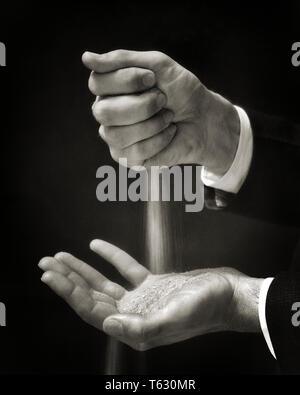 1930 simbólica de manos de un hombre sujetando las arenas del tiempo dejando caer DE UNA MANO A OTRA - s8433 HAR001 HARS ALTOS HOMBRE MEDIANA EDAD SENIOR B&W hombre de mediana edad éxito traje y corbata SUEÑOS UN PODEROSO CONOCIMIENTO LA OPORTUNIDAD DE DEJAR A las arenas del tiempo concepto Conceptual cerca ANCIANO IDEAS conceptos simbólicos mediados de mediados de hombre adulto adulto joven adulto hombre blanco y negro la etnia CAUCÁSICA HAR001 REPRESENTACIÓN ANTIGUA Imagen De Stock
