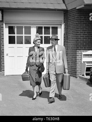 1950 par de moda vestidos caminando por la calzada llevar equipaje - S177 HAR001 HARS mujeres casadas maridos cónyuge SALUBRIDAD HOME VIDA AMISTAD ESPACIO COPIA DE LONGITUD COMPLETA PERSONAS DAMAS VARONES B&W PARTNER traje y corbata felicidad AVENTURA ESTILOS DE OCIO VIAJE CONEXIÓN Emoción Moda elegante moda cooperación mediados de adulto-adulto medio HOMBRE-MUJER ADULTA MEDIA COMPAÑERISMO ESPOSAS EN BLANCO Y NEGRO la etnia CAUCÁSICA HAR001 ANTICUADO Imagen De Stock