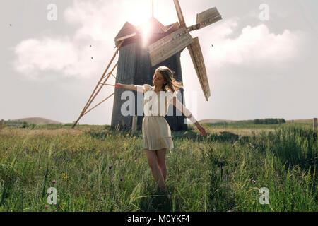 Mujer caucásica equilibrando en la hierba cerca de molino de viento Imagen De Stock