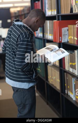 Negro macho joven estudiante universitario investiga los artículos en la biblioteca escolar. Imagen De Stock