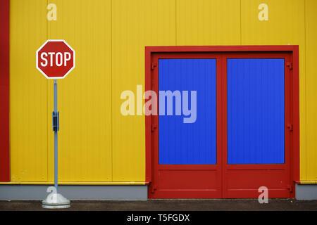 Un colorido y llamativo el flanco de un centro comercial con una entrada lateral y una señal de stop. Imagen De Stock