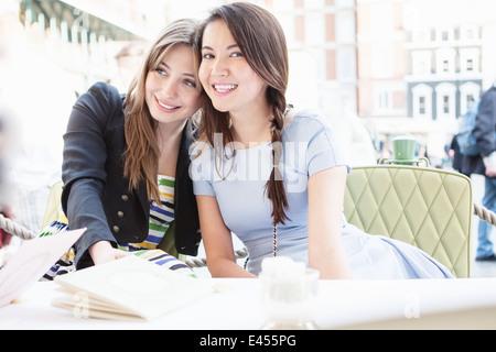 Las mujeres jóvenes sentados en una mesa en el restaurante al aire libre Imagen De Stock