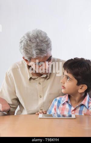Abuelo y nieto mediante tableta digital Imagen De Stock