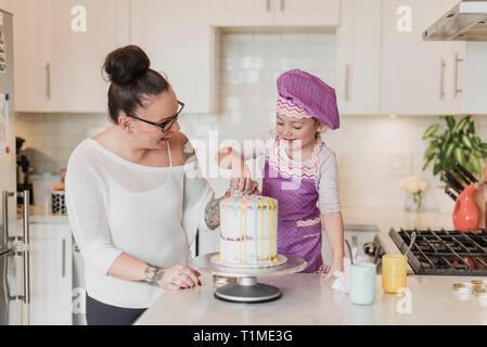 Madre e hija decorar pasteles en la cocina Imagen De Stock