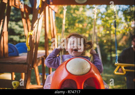 Chica con el pelo rojo balanceándose en el columpio, Retrato Imagen De Stock