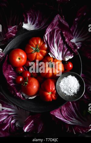Los tomates, la sal del mar y radicchio Imagen De Stock