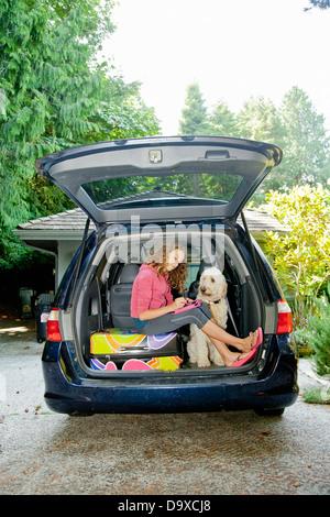 Jovencita con el equipaje y el perro en coche Imagen De Stock
