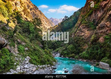 Langtang río en Nepal con el asentamiento humano en el fondo Imagen De Stock
