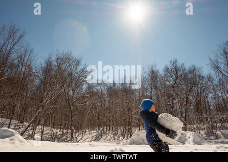 Muchacho portando una gigantesca bola de nieve, Estados Unidos Imagen De Stock