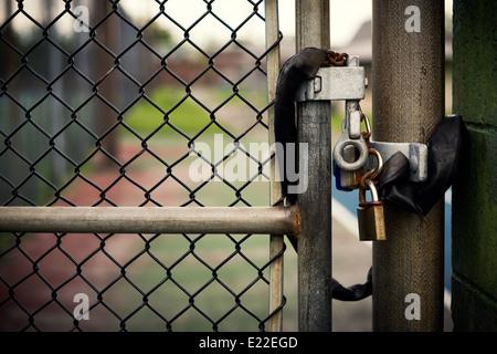Primer plano de un candado cerrado que fijan una cadena de metal de la puerta de enlace. Imagen De Stock