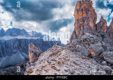 Vista desde Puez-Geisler reserva en los Alpes Dolomitas. Excursionista con perros de pie en el borde, ver las montañas. Imagen De Stock