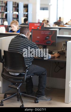 Los estudiantes universitarios que usan los ordenadores de la biblioteca. Imagen De Stock