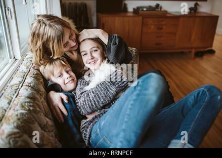 Retrato madre afectuosa y niños con cuy en el sofá de la sala Imagen De Stock