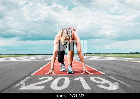 Corredoras espera a sus inicios en la pista de aterrizaje. En el primer plano el pintado de fecha 2019 simboliza el año. Imagen De Stock