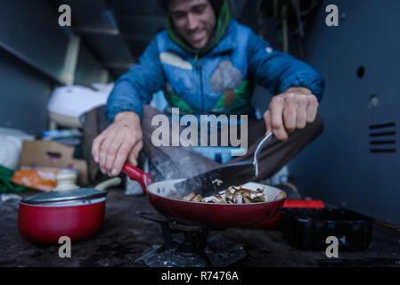 Macho joven escalador cocinar desayuno en autocaravana Imagen De Stock
