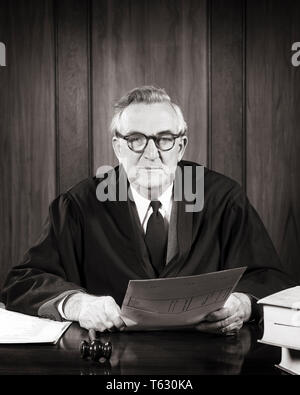 1940 1950 hombre serio juez sentado vistiendo túnica con martillo en mano sujetando los papeles mirando a la Cámara - s7404 HAR001 HARS COMUNICACIÓN MARTILLO LIFESTYLE ELDER TRABAJOS COPIA túnica media longitud espacial personas hombres confianza HOMBRE SENIOR SENIOR expresiones de adultos de mediana edad B&W hombre de mediana edad contacto ocular libertad traje y corbata de habilidades Habilidades de ocupación OLDSTERS antiguas togas judiciales potente liderazgo abogados juicio severo ABOGADOS OCUPACIONES AUTORIDAD POLÍTICA FISCAL CONCEPTUAL ancianos en blanco y negro de la cooperación directa de etnia CAUCÁSICA HAR001 ANTICUADO Imagen De Stock