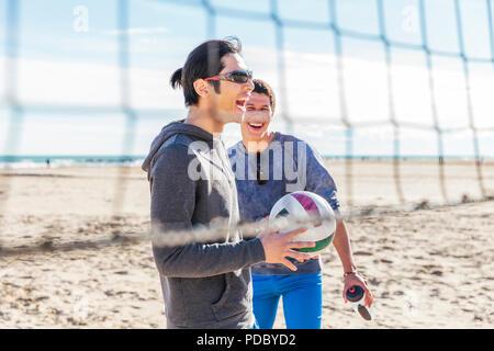 Feliz amigos varones jugando voleibol de playa en sunny beach Imagen De Stock