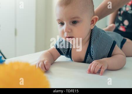 Cute kid alcanza para una pelota de juguete. La madre juega con el niño. El desarrollo del niño. El crecimiento de los niños Imagen De Stock