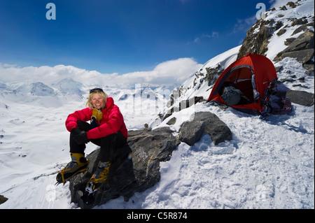 Un montañero en una roca relajante después de un duro día de escalada. Imagen De Stock