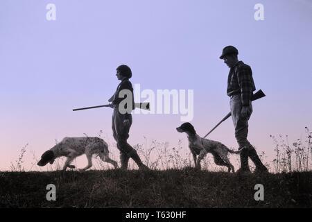 1920 1930 silueta anónima al hombre y a la mujer los cazadores que portan armas, cada uno con un perro de caza - S2541b HAR001 HARS SILUETAS DE OCIO Y RECREO CANINOS POOCH Conexión anónima COOPERACIÓN CANINA ARMA ARMAS DE FUEGO CAZADORES mamífero adulto medio hombre adulto medio Mediados de-MUJER ADULTA COMPAÑERISMO EN BLANCO Y NEGRO HAR001 ANTICUADO Imagen De Stock