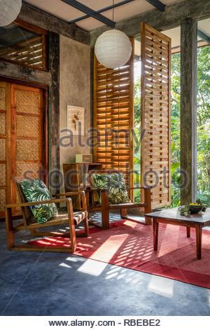 Salón con ventana al jardín. Jalakara Villa Hotel, Islas Andamán y Nicoar, India. Arquitecto: Ajith Andagere, 2016. Imagen De Stock