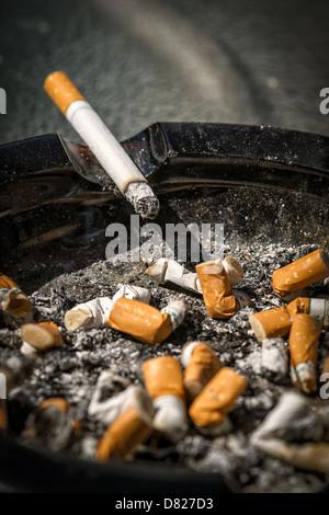 Un cigarrillo ardiendo con largas ash se encuentra sobre la ladera de una completa y muy sucio cenicero lleno de Imagen De Stock