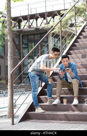 Los hombres jóvenes con café al aire libre Imagen De Stock